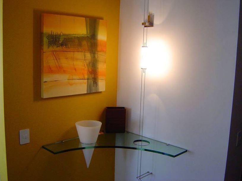 Destaque de elementos individuais: aplicamos uma cordoalha de 12V que atravessa o aparador de cristal 20mm, e a lâmpada bipino garante efeito cenográfico a este hall de entrada.